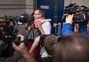 "Marc Emery receives a hug from his wife Jodie at the border crossing in Windsor, Ontario, Tuesday, August 12, 2014. Canada's self-styled ""Prince of Pot"" has returned home after serving his U.S. sentence for selling marijuana seeds to customers across the border. THE CANADIAN PRESS/ Geoff Robins"