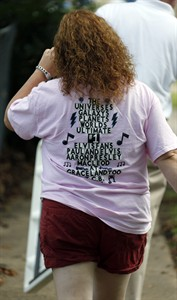 """A visitor wears a t-shirt adorned with the slogan the late Paul MacLeod, an Elvis-obsessed man who turned his antebellum home into the offbeat museum called Graceland Too, labeled himself as the """"world's greatest Elvis fan,"""" Tuesday, Aug. 12, 2014 in Holly Springs, Miss. MacLeod, who died July 17, was remembered during a afternoon and evening long memorial at his museum converted house that was filled with an eclectic collection of photos, records, albums and knick-knacks. The memorial is the same week of the anniversary of Presley's death on Aug. 16, 1977 at his Graceland mansion in Memphis. (AP Photo/Rogelio V. Solis)"""