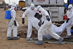 Health workers carry the body of a man suspected of dying from the Ebola virus and left in the street, in the capital city of Monrovia, Liberia, Tuesday, Aug. 12, 2014. The World Health Organization declared it's ethical to use untested drugs and vaccines in the ongoing Ebola outbreak in West Africa although the tiny supply of one experimental drug handed out to three people has been depleted and it could be many months until more is available. (AP Photo/Abbas Dulleh)