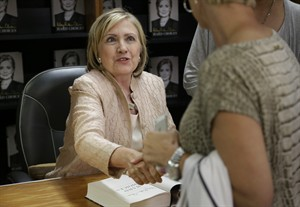 "Former Secretary of State Hillary Rodham Clinton shakes hands with a customer at Bunch of Grapes Bookstore, in Vineyard Haven, Mass., on the island of Martha's Vineyard, Wednesday, Aug. 13, 2014, during a book signing event for her memoir ""Hard Choices."" Hillary Rodham Clinton says she's looking forward to hugging out her differences with President Barack Obama. Obama's former secretary of state told reporters Wednesday that she's proud to have served with him despite some differences of opinion. (AP Photo/Steven Senne)"
