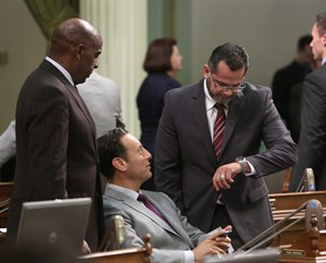 Assemblyman V. Manuel Perez, right, D-Coachella, checks the time as he talks with Assemblymen Steven Bradford, left, D-Gardena, and Roger Hernandez, D-West Covina, before a vote was taken on a revamped water bond measure for the November ballot, Wednesday, Aug. 13, 2014, in Sacramento, Calif. The Assembly approved the $7.5 billion measure and sent it to the Senate for a final vote. (AP Photo/Rich Pedroncelli)