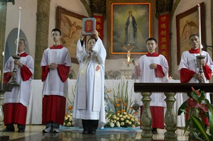 A Chinese priest holds up a bible during a mass at the 400-year-old Cathedral of the Immaculate Conception in Beijing, China, Friday, Aug. 15, 2014. Chinese Catholics on Friday cheered Pope Francis' visit to neighboring South Korea, saying they hoped his trip to their region would help end the estrangement between Beijing and the Vatican. However, China's entirely state-run media imposed a virtual news blackout on his visit, ensuring the public at large would know little about Francis' activities. (AP Photo/Ng Han Guan)