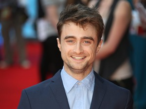 """FILE - In this file photo taken Tuesday, Aug. 12, 2014, British actor Daniel Radcliffe reacts, as he arrives on the red carpet for the UK premiere of What If, at the Odeon West End in central London. aniel Radcliffe says he finds the concept of celebrity and the level of interest in the trivia of actors' lives """"weird."""" While promoting his first romantic comedy _ """"What If,"""" directed by Michael Dowse _the 25-year-old British star was keen to keep the conversation away from his own love life. Radcliffe is rumored to be dating his """"Kill your Darlings"""" co-star Erin Drake. (Photo by Joel Ryan/Invision/AP)"""