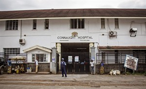 A security guard, center, stands outside the Connaught Hospital, where a leading doctor died from Ebola on Wednesday, in Freetown, Sierra Leone, Friday, Aug. 15, 2014. The Ebola outbreak that has killed more than 1,000 people in West Africa could last another six months, Doctors Without Borders said Friday, and a medical worker acknowledged that the true death toll is unknown. (AP Photo/Michael Duff)