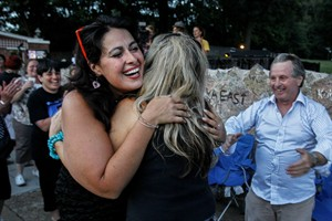 Sarah Kerendian, left, of New York City, hugs Patty Andersen, of Memphis, Tenn., after they danced to early Elvis songs outside the gates of Graceland during a candlelight vigil in remembrance of Elvis' death 37 years-ago, Friday, Aug. 15, 2014, in Memphis, Tenn. (AP Photo/The Commercial Appeal, Mark Weber)
