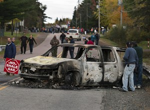 A burned police vehicle is seen in Rexton, N.B., as police began enforcing an injunction to end an ongoing demonstration against shale gas exploration in eastern New Brunswick on Thursday, Oct.17, 2013. Federal officials closely tracked the fallout of an RCMP raid on a First Nations protest against shale-gas exploration in New Brunswick, at one point raising concerns it could spawn another countrywide movement like Idle No More. THE CANADIAN PRESS/Andrew Vaughan