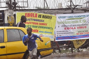 People pass by Ebola virus health warning signs, in the city of Monrovia, Liberia, Sunday, Aug. 17, 2014. Liberian officials fear Ebola could soon spread through the capital's largest slum after residents raided a quarantine center for suspected patients and took items including blood-stained sheets and mattresses. The violence in the West Point slum occurred late Saturday and was led by residents angry that patients were brought from other parts of the capital to the holding center, Tolbert Nyenswah, assistant health minister, said Sunday. (AP Photo/Abbas Dulleh)