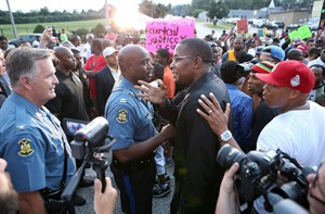 Col. Ron Replogle, left, and Capt. Ron Johnson talk with Malik Shabazz, president of the Black Lawyers for Justice, (center) during a march with protesters along W. Florissant Avenue in Ferguson Missouri on Saturday, Aug. 16, 2014. (AP Photo/St. Louis Post-Dispatch, David Carson)