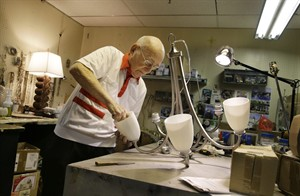 "Lighting repair specialist Herman ""Hy"" Goldman, 101, refurbishes a light fixture in his workshop at Capitol Lighting where he has worked for 73 years, Monday, Aug. 18, 2014, in East Hanover, N.J. Now that he has turned 101, Goldman who often said that he would retire when he reached 100, has changed his mind. He still drives himself to work four days a week. (AP Photo/Mel Evans)"