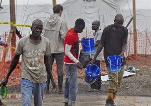 Health workers receive buckets, as part of their Ebola virus prevention protective gear, at an Ebola treatment center in the city of Monrovia, Liberia, Monday, Aug. 18, 2014. Liberia's armed forces were given orders to shoot people trying to illegally cross the border from neighboring Sierra Leone, which was closed to stem the spread of Ebola, local newspaper Daily Observer reported Monday. (AP Photo/Abbas Dulleh)