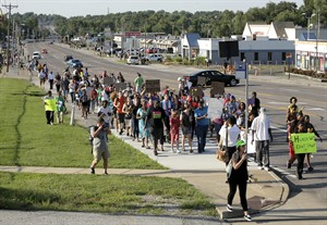 """Protesters march Tuesday, Aug. 19, 2014, for Michael Brown, who was killed by police Aug. 9 in Ferguson, Mo. Ferguson's leaders urged residents Tuesday to stay home after dark to """"allow peace to settle in"""" and pledged several actions to reconnect with the predominantly black community in the St. Louis suburb where the fatal shooting of 18-year-old Michael Brown has sparked nightly clashes between protesters and police. (AP Photo/Charlie Riedel)"""