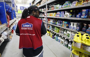 FILE - In this Nov. 14, 2011 file photo, a Lowe's employee walks down an aisle in the store in Saugus, Mass. Lowe's reports quarterly earnings on Wednesday, Aug. 20, 2014. (AP Photo/Michael Dwyer, File)