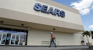 FILE - In this Friday, Nov. 9, 2012, file photo, a customer walks towards a Sears store in Hialeah, Fla. On Thursday, Aug. 21, 2014, Sears Holdings Corp. is scheduled to report quarterly financial results before the market opens. (AP Photo/Alan Diaz, File)