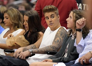 FILE - This May 11, 2014 file photo shows singer Justin Bieber, second from right, watching the Los Angeles Clippers play the Oklahoma City Thunder with his mother Pattie Mallette, second from left, in the first half of Game 4 of the Western Conference semifinal NBA basketball playoff series in Los Angeles. Photographer Aja Oxman sued Bieber and his bodyguard Dwayne Patterson for assault and intentional infliction of emotion distress in Los Angeles on Wednesday, Aug. 20, over an altercation last year on Hawaii's Shipwreck Beach. The lawsuit states Patterson injured Oxman while trying to forcibly retrieve a camera memory card after Bieber spotted the photographer snapping photographs of him leaping off a cliff into the ocean. (AP Photo/Mark J. Terrill, File)