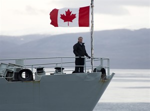Canadian Prime Minister Stephen Harper stands on the bow of the HMCS Kingston as it sails in the Navy Board Inlet Sunday August 24, 2014. THE CANADIAN PRESS/Adrian Wyld