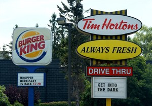 A Burger King sign and a Tim Hortons sign are displayed on St. Laurent Boulevard in Ottawa on Monday, August 25, 2014. Shares in Burger King and Tim Hortons have jumped dramatically on news the two fast-food companies are talking about joining forces, a move that could help the iconic coffee and doughnut chain improve its chances of expanding successfully in the U.S. THE CANADIAN PRESS/Sean Kilpatrick