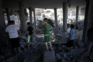 Palestinians walk amid the rubble of the Omar Ibn Abdul Aziz mosque after it was hit by an Israeli strike in Gaza City, Monday, Aug. 25, 2014. (AP Photo/Khalil Hamra)