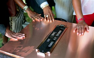 FILE - In this Monday, Aug. 25, 2014, file photo, family members touch the copper top of the vault containing the casket of Michael Brown during his funeral in Normandy, Mo. Hundreds of people gathered to say goodbye to Brown, who was shot and killed by a Ferguson, Mo., police officer on Aug. 9. (AP Photo/St. Louis Post Dispatch, Robert Cohen, Pool)