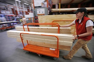 In this May 17, 2014 photo, a shopper checks out with her lumber at a Home Depot in Boston. The Conference Board reports on consumer confidence in August on Tuesday, Aug. 26, 2014. (AP Photo/Gene J. Puskar)