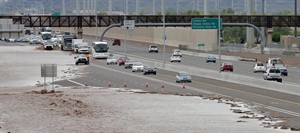 FILE - This Aug. 19, 2014 file photo shows flash flood waters from the overrun Skunk Creek flood I-10 in northwestern Phoenix. Global warming is here, human-caused and can already be considered dangerous, a draft of a new international science report says, warning that it is increasingly likely that climate change could be irreversible. The United Nations' Intergovernmental Panel on Climate Change on Monday sent governments a final draft of its synthesis report, which combines three earlier, gigantic documents by the Nobel Prize-winning group. There is little in the report, that wasn't in the other more-detailed versions, but the language is more stark and the report attempts to paint a bigger picture of the problem caused by the burning of fossil fuels, such as coal, oil and gas. (AP Photo/Matt York, File)