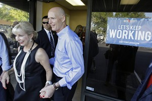 Florida Gov. Rick Scott, right, and his wife Ann, depart after a visit to a phone bank field office thanking volunteers for their work and support, Tuesday, Aug. 26, 2014, in Orlando, Fla. Scott is seeking re-election for a second term as Florida's governor. (AP Photo/John Raoux)