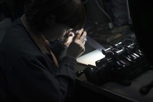 Shoko Ideriha, a film process technician in charge of archive, checks the negative of a movie prior to scanning for digitization at Tokyo Laboratory Ltd. in Tokyo, Wednesday, Aug. 27, 2014. At the humble Tokyo laboratory, Godzilla, including the 1954 black-and-white original, is stomping back with a digital makeover that delivers four times the image quality of high definition. Experts say the chemical reactions used to make old movies stored far greater detail than was visible with the limited projection technology of the era, as well as with subsequent digital updates. (AP Photo/Eugene Hoshiko)