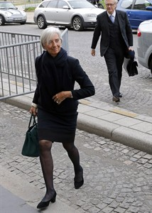"""FILE - In this March 19, 2014 file photo, International Monetary Fund chief Christine Lagarde arrives at a courthouse, in Paris, Wednesday, March 19, 2014. Lagarde says she is under official investigation for negligence in a French corruption probe that dates back to her days as finance minister. In a statement released Wednesday, Aug.27, 2014 after a fourth round of questioning before magistrates, Lagarde said she was returning to her work in Washington later in the day and said the decision was """"without basis."""" She and her former chief of staff face questions about their role in a 400 million-euro ($531 million) payment to a businessman. (AP Photo/Christophe Ena, File)"""