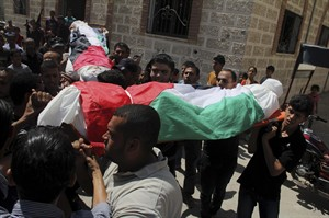 Palestinian relatives carry national flag-draped bodies of Omar al-Bareem, 17, and his brother Mohammed, 12, who were killed in an Israeli strike on a car, during their funeral at their family house in Khan Younis, in the southern Gaza Strip, Wednesday, Aug. 27, 2014. Two brother were killed in an airstrike on a car yesterday east of Khan Younis, according to Gaza health official Ashraf al-Kidra. (AP Photo/Hatem Ali)