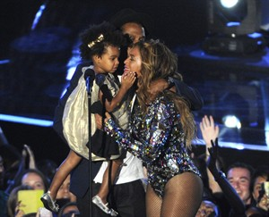 "FILE - In this Sunday, Aug. 24, 2014 file photo, Beyonce on stage hugs Jay Z and their daughter Blue Ivy as she accepts the Video Vanguard Award at the MTV Video Music Awards at The Forum, in Inglewood, Calif. BET has suspended a producer after a joke about Blue Ivy's hair aired Monday, Aug. 25, 2014, on the network's music video countdown show, ""106 & Park."" A source at the network, who spoke on the condition of anonymity because the person was not allowed to discuss the matter publicly, said the producer was suspended after the ill-fitting joke about Beyonce and Jay Z's two-year-old daughter aired. (Photo by Chris Pizzello/Invision/AP, file)"