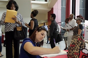 In this photo taken Tuesday, Aug. 19, 2014, Jessica Pimentel, of Hollywood, Fla., fills out a job application during a job fair in Sunrise. Fla. The Labor Department releases weekly jobless claims on Thursday, Aug. 28, 2014. (AP Photo/Alan Diaz)