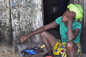 In this photo taken on Wednesday, Aug. 27, 2014, a woman sits next to her home with coals packed on her fire place, in the West Point area that has been hit hard by the Ebola virus, with residents not allowed to leave West Point, as government forces clamp down on movement to prevent the spread of Ebola, in Monrovia, Liberia. The Ebola outbreak in West Africa eventually could exceed 20,000 cases, more than six times as many as are now known, the World Health Organization said Thursday. A new plan released by the U.N. health agency to stop Ebola also assumes that the actual number of cases in many hard-hit areas may be two to four times higher than currently reported.( AP Photo/Abbas Dulleh)
