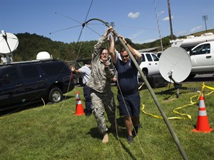 U.S. Army Sgt. David Adams, left, and a group of firefighters raise a long-range antenna outside the Deerfield Valley Volunteer Fire Department to help communicate with aircraft in the area on Thursday, Aug. 28, 2014 in Deerfield, Va. The pilot of an F-15 jet that crashed this week in remote Virginia mountains was killed, military officials said Thursday, bringing to a sad end an exhaustive two-day search involving more than 100 local, state and federal officials as well as volunteers. (AP Photo/The Staunton News Leader, Griffin Moores)