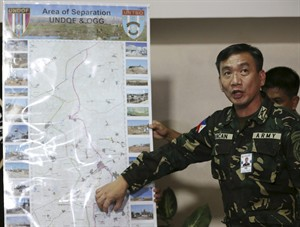 Filipino Col. Roberto Ancan, Commanding Officer of the Armed Forces of the Philippines Peacekeeping Operations Center, points to an area of a map where Filipino peacekeepers are stationed in Golan heights during a press conference at Camp Aguinaldo military headquarters in suburban Quezon city, Philippines on Friday, Aug. 29, 2014. The United Nations said Friday that as well as the 43 detained Fijian soldiers, another 81 Philippine peacekeepers had been effectively trapped after being restricted to their positions by militants in the vicinity of Ar Ruwayhinah and Burayqah. (AP Photo/Aaron Favila)