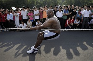 "North Koreans watch as former NFL player Bob ""The Beast"" Sapp pulls on a rope attached to a bus on the sidelines of a pro wrestling exhibition Friday, Aug. 29, 2014 in Pyongyang, North Korea. Former NFL player Sapp and a group of brawny pro wrestlers led by a Japanese politician took their oddball attempt at sports diplomacy to the streets of Pyongyang on Friday, staging a tug-war and arm wrestling competition with local children before a large and somewhat bewildered crowd of spectators. (AP Photo/Wong Maye-E)"