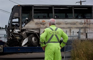 A Commercial Vehicle Safety and Enforcement officer watches as a tour bus that rolled over and crashed on the Coquihalla Highway south of Merritt, B.C., Thursday, is moved during an investigation at a towing company lot in Kelowna on Friday August 29, 2014. Dozens of the 56 people on the bus were injured, seven are listed in critical condition, six others are serious and 11 have non life-threatening injuries. THE CANADIAN PRESS/Darryl Dyck