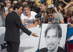 Actor Chris Messina looks at a giant portrait of Al Pacino as he arrives for the screening of the movie 'Manglehorn' at the 71st edition of the Venice Film Festival in Venice, Italy, Saturday, Aug. 30, 2014. (AP Photo/Andrew Medichini)