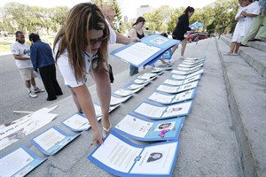 Bernadette Smith the sister of Claudette Osborne who has been missing since 2008 lays placards, of 94 women who have been murdered or are missing in Manitoba, at the Manitoba Legislature in Winnipeg, Wednesday, August 26, 2009. A woman whose sister vanished six years ago is leading a group of volunteers who plan to dredge the Red River for missing and murdered aboriginal women. THE CANADIAN PRESS/John Woods