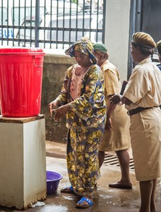 In this photo taken on Friday, Aug. 29, 2014, a woman washes her hands in chlorinated water at the Connaught Hospital, which has suffered the loss of medical workers in the past from the Ebola virus, in Freetown, Sierra Leone. Dr. Sheik Humarr Khan was one of those on the front lines of the Ebola outbreak. The tireless Khan was jovial but forceful, doling out praise and criticism to junior doctors at his hospital. But Khan became infected and died, and so have at least 120 other medical workers in Sierra Leone and in three other countries, creating immediate and long-term impacts in a region that already had an understaffed and under equipped health care system. (AP Photo/ Michael Duff)
