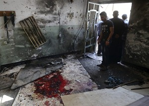 Worshipers look at blood stains inside the Imam Ali mosque after a suicide bomb attack in New Baghdad, Iraq, Monday, Aug. 25, 2014. Iraqi officials say a wave of attacks targeting commercial areas in and outside Baghdad has killed and wounding scores of people. They say the deadliest of Monday's bombings was carried out by a suicide bomber who blew up himself among Shiite worshippers who were leaving Imam Ali mosque after noon prayers in the capital's eastern New Baghdad area, killing over a dozen people and wounding many others. (AP Photo/ Khalid Mohammed)