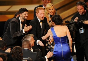"""Gail Mancuso accepts the award for outstanding directing for a comedy series for her work on """"Modern Family"""" at the 66th Annual Primetime Emmy Awards at the Nokia Theatre L.A. Live on Monday, Aug. 25, 2014, in Los Angeles. Looking on from left are Justin Mikita, Jesse Tyler Ferguson and Julie Bowen. (Photo by Chris Pizzello/Invision/AP)"""