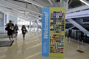 Three people walk past a welcome sign for the 9th International Gay Games inside the downtown convention center in Cleveland Thursday, Aug. 7, 2014. Cleveland and Akron might seem like odd choices to host the games, but organizers of the weeklong, Olympic-style event say that's exactly the point. There are hopes that bringing the Games to the Rust Belt will help chip away at barriers that persist between the gay and straight communities. (AP Photo/Mark Duncan)