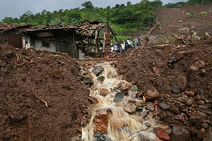 Villagers watch a rescue operation standing by mud and slush at the site of a landslide in Malin village, in the western Indian state of Maharashtra, Friday, Aug. 1, 2014. Heavy rains hampered efforts Friday by hundreds of rescue workers digging through heavy mud and debris, as the death toll from a landslide that engulfed an entire village in western India crossed 50. (AP Photo/Rafiq Maqbool)