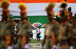 A schoolgirl holds an umbrella in the rain and watches soldiers marching during a parade celebrating India's Independence Day in Gauhati, India, Friday Aug. 15 2014. India celebrates its 1947 independence from British colonial rule on Aug. 15. (AP Photo/Anupam Nath)