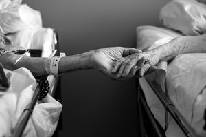In this July, 2014 photo provided by their granddaughter Melissa Stone, Don Simpson, 90, and his wife Maxine, 87, hold hands from adjoining hospice beds in Sloan's home in Bakersfield, Calif. The couple, married 62 years, died four hours apart July 21, 2014, while lying next to each other, their family said. (AP Photo/Melissa Sloan