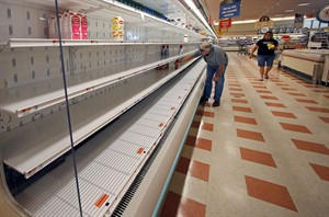 A shopper reaches into a mostly empty dairy shelf at Market Basket in Haverhill, Mass., Monday, Aug. 18, 2014. As an employee revolt at the New England grocery store chain headed into its fifth week, the governors of Massachusetts and New Hampshire made the unusual move of personally stepping into negotiations aimed at ending a standoff threatening the future of the popular low-priced supermarkets. (AP Photo/Elise Amendola)
