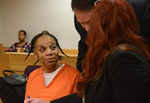 In a photo from Monday, Aug. 11, 2014, Cheryl White listens to her attorneys, Jeff and Kimberly Schroder, during a court hearing in Battle Creek, Mich. White, who was charged with stabbing the father of R&B singer Mary J. Blige has been ordered to stand trial. The Battle Creek Inquirer reports that White faces up to life in prison if convicted of assault with attempt to murder. White's boyfriend, 63-year-old Thomas Blige, testified and said White attacked him with a knife after he caught her slashing his tires. Blige says he was cut on the throat, lung and arm. (AP Photo/Battle Creek Enquirer, Trace Christenson)