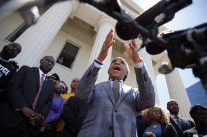 Civil rights activist Rev. Al Sharpton speaks during a news conference outside the Old Courthouse Tuesday, Aug. 12, 2014, in St. Louis. Michael Brown Jr., 18, who was unarmed, was shot to death Saturday by a Ferguson police officer while walking with a friend down the center of the street. (AP Photo/Jeff Roberson)