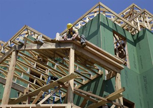In this Wednesday, July 30, 2014 photograph, a builder works on the construction of new homes in Belmar, N.J. U.S. home construction rebounded in July, rising to the fastest pace in eight months and offering hope that housing has regained momentum after two months of declines. (AP Photo/Mel Evans)