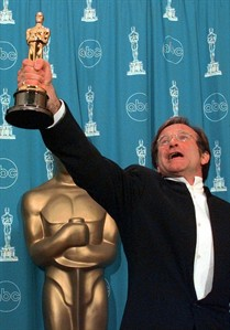 "FILE - This March 23, 1998 file photo shows Robin Williams holding his Oscar high backstage at the 70th Academy Awards at the Shrine Auditorium in Los Angeles after won Best Supporting Actor for ""Good Will Hunting."" Williams, whose free-form comedy and adept impressions dazzled audiences for decades, has died in an apparent suicide. He was 63. The Marin County Sheriff's Office said Williams was pronounced dead at his home in California on Monday, Aug. 11, 2014. The sheriff's office said a preliminary investigation showed the cause of death to be a suicide due to asphyxia. (AP Photo/Reed Saxon, File)"