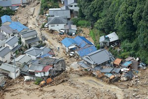 In this aerial photo, houses are heavily damaged after a massive landslide swept through residential areas in Hiroshima, western Japan, Wednesday, Aug. 20, 2014. A several people died and at least a dozen are missing after rain sodden hills in the outskirts of Hiroshima gave way in at least five landslides, according to The Japanese broadcaster NHK. (AP Photo/Kyodo News, Shingo Nishizume) JAPAN OUT, MANDATORY CREDIT